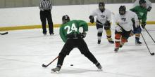 Hockey player in green preparing to shoot.