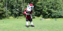 Gee-Gees Mascot on a Golf Court swinging a club.