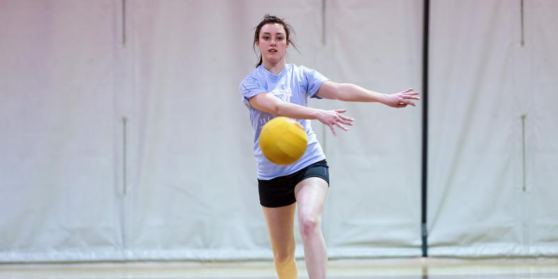 Girl throwing a dodgeball.